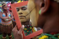 An Indigenous man applies body paint during an annual three-day campout protest known as the Free Land Encampment, in Brasilia, Brazil in 2019. (Eraldo Peres/AP)