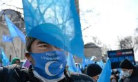 A protester from the Uyghur community living in Turkey, holds an anti-China placard during a protest in Istanbul, on 25 March. Photograph: Bülent Kılıç/AFP/Getty Images