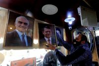 A frame maker hangs pictures of King Abdullah II in Amman, Jordan, on Sunday. (Mohammad Ali/EPA-EFE/REX/Shutterstock)