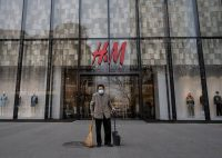 A street cleaner stands in front of an H&M clothing store last month in Beijing. (Kevin Frayer/Getty Images)