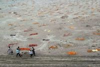 Relatives carry a body for cremation past the graves of people believed to be covid-19 victims on the banks of the Ganges River in Shringverpur, India, on May 20. (Ritesh Shukla/Getty Images)
