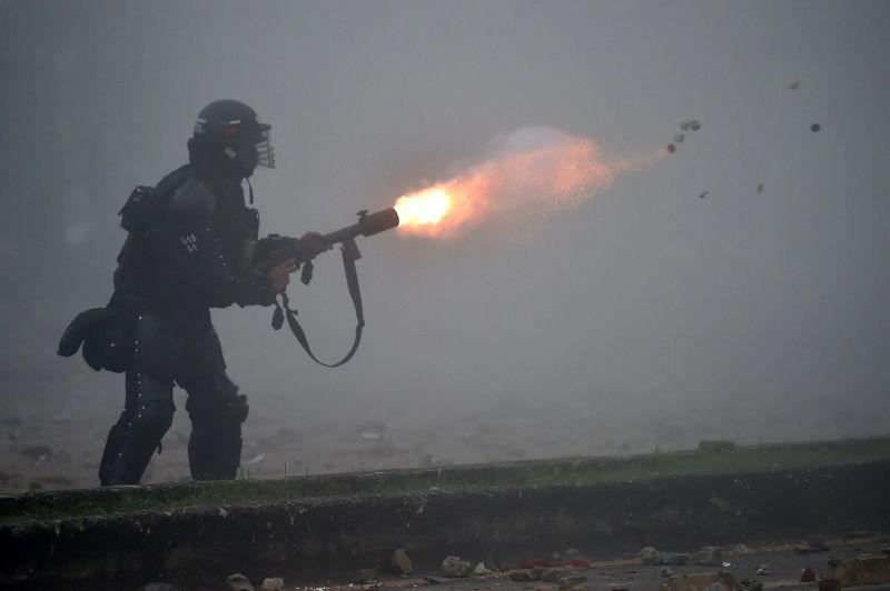 Un policía dispara gases lacrimógenos a manifestantes en Cali el 3 de mayo. Credit Luis Robayo/Agence France-Presse — Getty Images