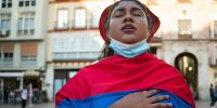 Protester wrapped in a Colombian flag sings a hymn during a demonstration against the government of President Iván Duque. Photo by Jesus Merida/SOPA Images/LightRocket via Getty Images.