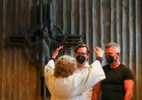 Pastoral worker Brigitte Schmidt blesses Ralf-Michael Berger and Andreas Helfrich in a Catholic church in Cologne, Germany, on May 10. (Thilo Schmuelgen/Reuters)