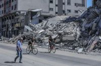 Palestinians ride bicycles past a destroyed building in Gaza City on Tuesday. (Mohammed Saber/EPA-EFE/REX/Shutterstock)