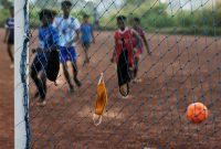 Children hang their face masks in the net and play a game of soccer in Kochi, Kerala state, India, on Oct. 6. (R S Iyer/AP)