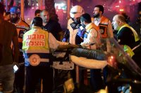 Israeli medics evacuating a wounded man after a rocket fired from the Gaza Strip hit the central Israeli town of Holon, near Tel Aviv. Credit Avshalom Sassoni/Maariv, via Associated Press