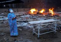 A woman mourning her husband at a cremation site for victims of Covid in New Delhi. Credit Adnan Abidi/Reuters