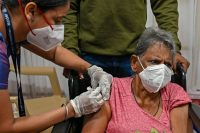A woman getting the Covid-19 vaccine in Mumbai, India. Credit Punit Paranjpe/Agence France-Presse — Getty Images