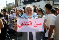 """An Iraqi protester carries a plascard reading in Arabic """"Who killed me?"""" in Baghdad during an anti-government demonstration against a wave of assassinations on May 25. (Ahmed Jalil/EPA-EFE/REX/Shutterstock)"""