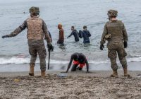 Soldados españoles junto a inmigrantes que han cruzado a nado por la frontera del Tarajal, en Ceuta, este martes.Javier Bauluz