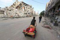 Un niño palestino transporta a otro en un carrito en Gaza, el pasado 14 de mayo.MOHAMMED SALEM / REUTERS