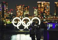 A couple poses for a selfie with an Olympic Rings monument at Odaiba Marine Park in Tokyo on Wednesday. (Kimimasa Mayama/EPA-EFE/Shutterstock)