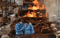 Familiares de una persona que murió por la COVID-19 en un sitio de cremación en la India. Credit Samuel Rajkumar/Reuters