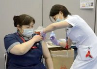 A nurse receives the first dose of the Pfizer coronavirus vaccine at Fujita Health University Hospital in Toyoake, Aichi prefecture, central Japan, on March 8. (Kyodo News via AP)