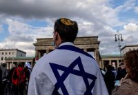 """A man wearing a kippah attends a rally themed """"solidarity with Israel and against antisemitism"""" in front of the Brandenburg Gate in Berlin on Thursday. (Filip Singer/EPA-EFE/Shutterstock)"""