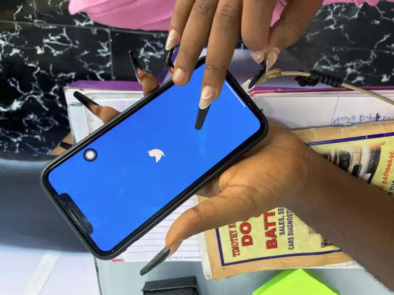 Ogechi Egemonu, an entrepreneur based in Lagos, Nigeria, opens the Twitter app on a smartphone at her office June 10. Many Nigerian companies use Twitter to conduct business, which means the official Twitter ban puts their work at risk. (Seun Sanni/Reuters)
