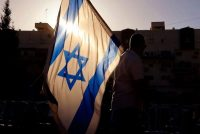 Right-wing supporters of Israeli Prime Minister Benjamin Netanyahu wave the national flag during a demonstration against the coalition to form a government, in the central Israeli city of Petah Tikva, on Thursday. (Jack Guez/AFP/Getty Images)