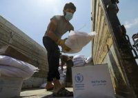 A worker unloads humanitarian aid from a truck in Idlib, Syria, on June 9. (Khalil Ashawi/Reuters)