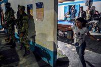 Soldados colombianos montan guardia mientras exguerrilleros de las FARC y lugareños juegan al billar en Antioquia, Colombia, en julio de 2020. (Joaquin Sarmiento/AFP vía Getty Images)