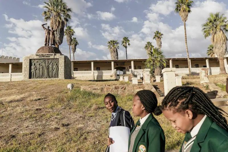 Namibian schoolgirls walk by a memorial to the victims of the genocide committed by German forces against Herero and Nama people in Windhoek, Namibia, in June 2017. (Gianluigi Guercia/AFP/Getty Images)