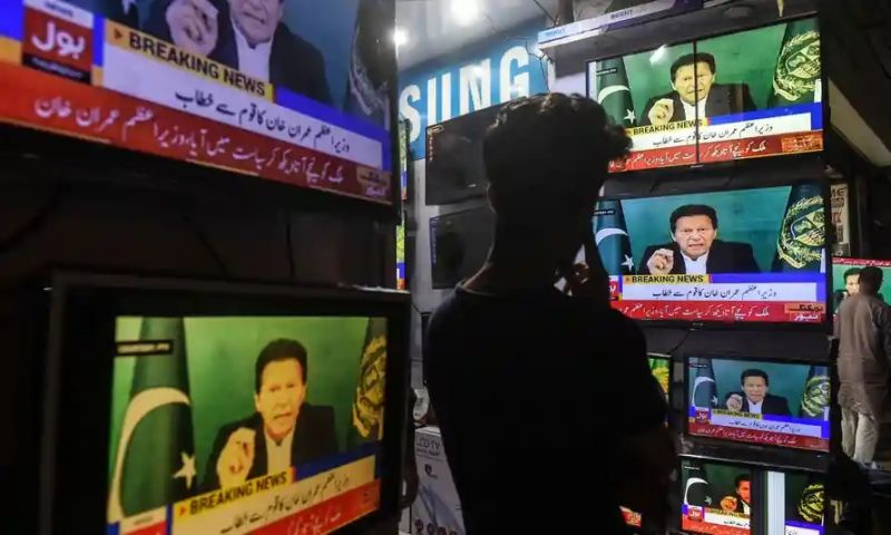 A shopkeeper watches Pakistan's prime minister Imran Khan on television, Karachi, March 2021. Photograph: Asif Hassan/AFP/Getty Images