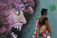 A pedestrian walks past a mural for front-line workers in Navi Mumbai, India, on Monday. (Indranil Mukherjee/AFP/Getty Images)
