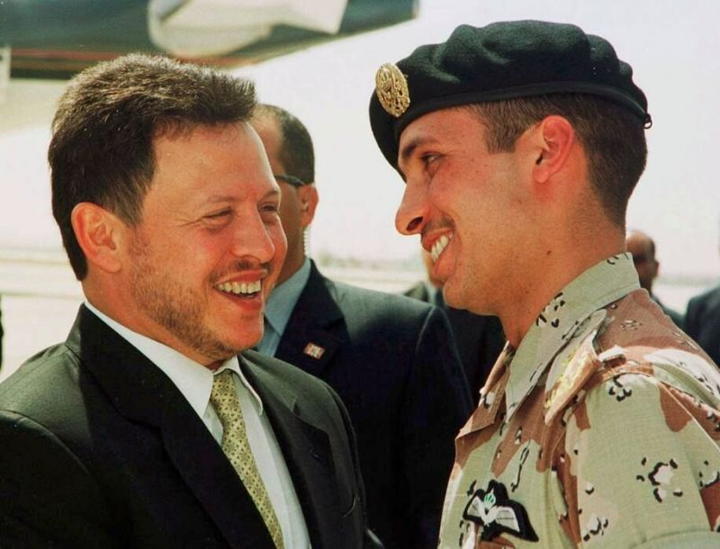 Jordan's King Abdullah II laughs with his half brother Prince Hamzah, right, shortly before the monarch embarked on a tour of the United States in 2001. (Yousef Allan/AP)