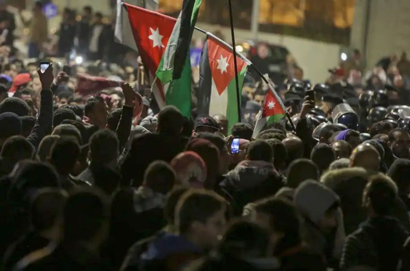 Jordanian protesters wave their national flag as they are confronted by riot police in the capital, Amman, in December 2018 during a demonstration against the government's decision to raise the income tax.. (Khalil Mazraawi/AFP via Getty Images)