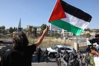 A protester waves a Palestinian flag near a police checkpoint at the entrance to the Sheikh Jarrah neighborhood in East Jerusalem on Friday. (Ahmad Gharabli/AFP/Getty Images)