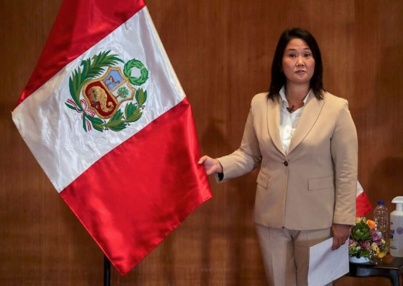 La candidata a la presidencia del Perú, Keiko Fujimori, quien se enfrentará a Pedro Castillo en una segunda vuelta en las elecciones del 6 de junio, sostiene la bandera nacional durante un evento con Castillo en Lima, Perú, el 17 de mayo de 2021. (REUTERS/Sebastian Castaneda/File Photo)