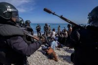 Migrants are surrounded by Spanish police near the border of Morocco and Spain, at the Spanish enclave of Ceuta, on May 18. (Bernat Armangue/AP)