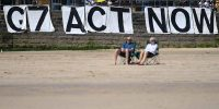 Environmental activists attach a banner calling on G7 leaders to act on climate change on the beach in St Ives, Cornwall during the G7 summit on 13 June 2021. Photo: Getty Images.