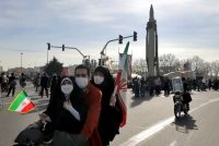 Iranians drive past a missile during a rally marking the 42nd anniversary of the Islamic Revolution, at Azadi (Freedom) Square in Tehran, on Feb. 10. (Ebrahim Noroozi/AP)