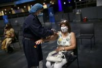 A health worker checks the vital signs of a woman who received a dose of the Pfizer-BioNTech coronavirus vaccine at Movistar Arena in Bogota on June 16. (Luisa Gonzalez/Reuters)