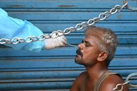 A health worker tests a man for the coronavirus at a market in Chennai, India, on Tuesday. (Arun Sankar/AFP/Getty Images)