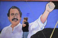 A woman walks past a mural depicting Nicaraguan President Daniel Ortega in Managua on Monday. (Stringer/Reuters)