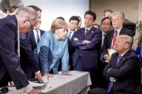 German Chancellor Angela Merkel, center, speaks to then-President Donald Trump during the June 2018 Group of Seven summit in Quebec, Canada. (Jesco Denzel/AP)