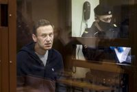 Russian opposition leader Alexei Navalny sits in a cage during a hearing Feb. 12 on his charges of defamation in the Babuskinsky District Court in Moscow. (Babuskinsky District Court Press Service via AP) (AP)