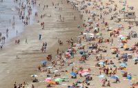 Turistas en la Playa del Inglés, al sur de Gran Canaria, este mes. Credit Borja Suarez/Reuters