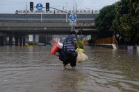 A man wades through a heavily flooded area after a strong downpour hit Shanghai on June 17, 2015. (Str/AFP/Getty Images)