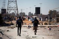 Two members of the South African Police Service try to disperse alleged looters outside the Chris Hanni Mall in Vosloorus on July 14. (Guillem Sartorio/AFP/Getty Images)