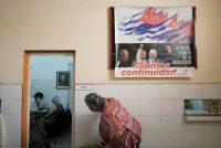 Una mujer pregunta sobre su turno para olivar la vacuna contra el COVID-19 debajo de un cartel que muestra imágenes de Fidel Castro, Raúl Castro y el presidente cubano Miguel Díaz-Canel con un cartel que dice: 'Somos continuidad', en un centro de vacunación en La Habana, Cuba, 23 de junio de 2021. (REUTERS/Alexandre Meneghini)