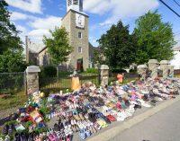Flores y zapatos infantiles colocados frente a una iglesia en protesta tras el hallazgo de los restos de 215 niños en un orfanato.Andre Pichette / EFE