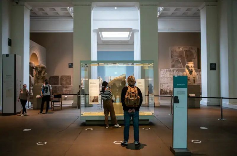 Visitors look at the Rosetta Stone next to social distancing markers on the floor at the British Museum in August 2020 in London. (Chris J. Ratcliffe/Getty Images)