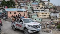 A police car filled with civilians and policemen drives up the Jalousie township where men accused of being involved in the assassination of President Jovenel Moise, have been arrested on July 8, 2021 at the Jalousie township in Haiti. Valerie Baeriswyl / AFP
