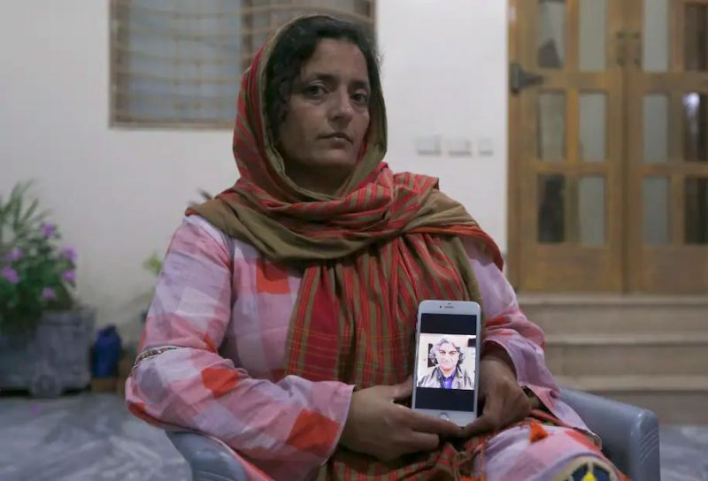 Kaneez Sughra, wife of kidnapped Pakistani journalist Matiullah Jan, shows a photo of her husband to journalists in Islamabad, Pakistan, on July 21, 2020. (Anjum Naveed/AP)