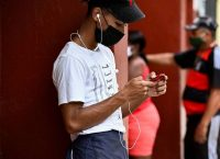 A young man uses his phone on a street in Havana this month. (Yamil Lage/AFP)