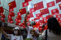 Pedestrians in Hong Kong take selfies with the flags of China and the Hong Kong Special Administrative Region on Wednesday ahead of the anniversary of the territory's return to China. (Lam Yik/Bloomberg News)