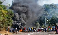Looters outside a shopping center alongside a burning barricade in Durban, South Africa on July 12. (Andre Swart/AP)